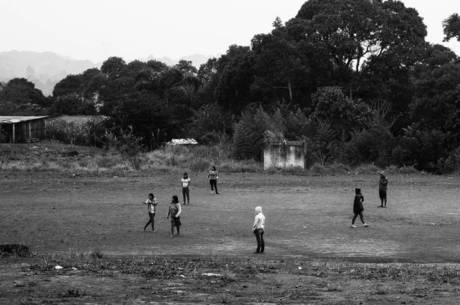 População indígena joga futebol em campo dentro da aldeia
