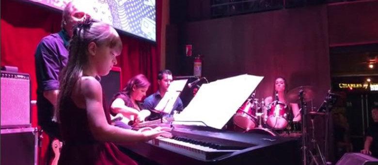 Rafinha Justus tocando piano em apresentação, ao lado do pai, Roberto Justus
