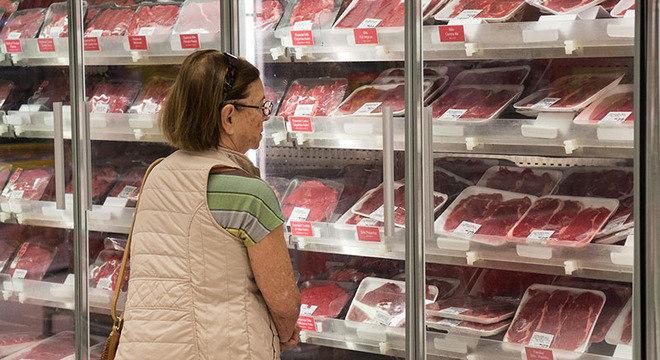 Consumidora escolhe carne em supermercado de SP. Ações da JBS e BRF recuam nesta segunda