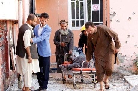 Funcionários de emissora estatal atacada por homens armados transportam corpo de um dos quatro mortos no atentado, que aconteceu no Afeganistão