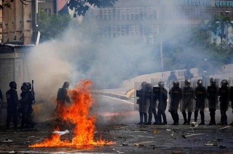 Forças de segurança se movimentam durante confronto com manifestantes em Caracas , na Venezuela, nesta quinta-feira