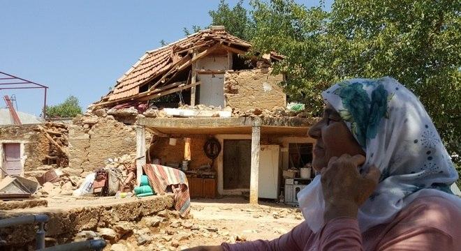 Uma mulher vê sua casa danificada após terremoto na vila de Yaliciftlik, perto da cidade turística de Bodrum, na Turquia