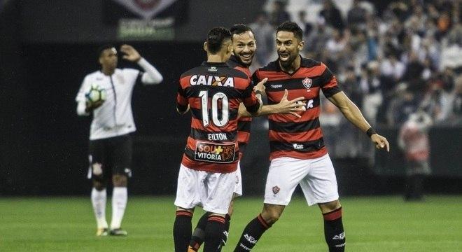 Jô (ao fundo) lamenta, enquanto jogadores do Vitória comemoram gol