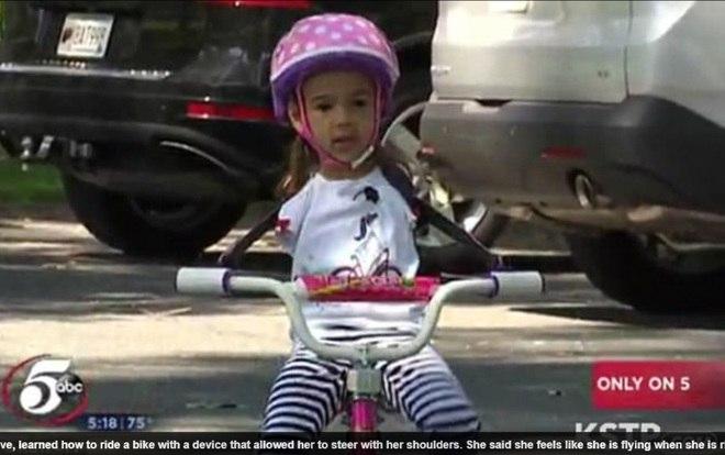 Por causa disso, os especialistas criaram um dispositivo feito de tubos e aparelhos de PVC, que é envolvido nas costas da menina e encaixada nas barras da bicicleta rosa e roxa
