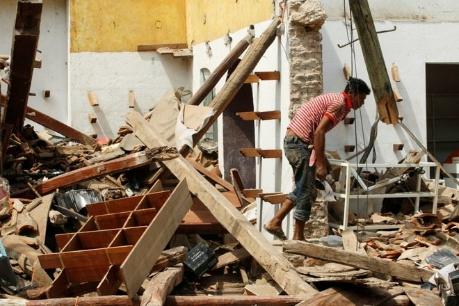 Homem caminha entre os destroços de uma casa destruída em um terremoto que atingiu a costa sul do México no final de quinta-feira, em Juchitan