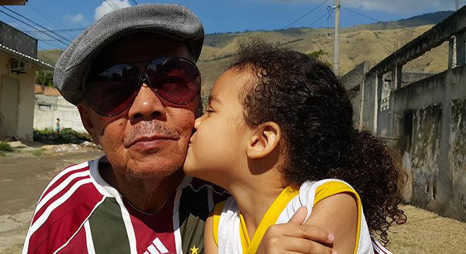 Maurício, acompanhado por sua neta, posa para a reportagem na rua de sua casa