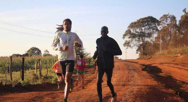 Ademir, de jaqueta branca, corre ao lado de um queniano