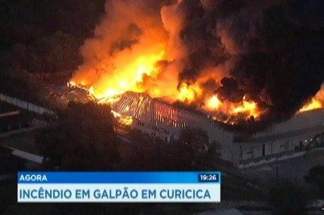 Bombeiros tentam controlar as chamas em galpão