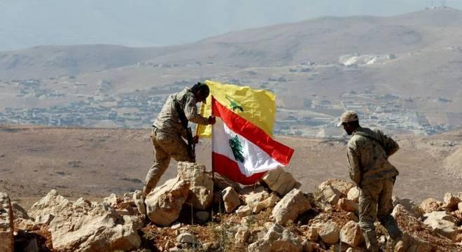 Membros do grupo Hezbollah fincam bandeiras na fronteira entre o Líbano e a Síria