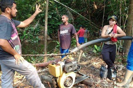Ageu Pereira (à esquerda), o presidente da comunidade de Montanha e Mangabal, explica a mineradores que terra pertence à comunidade
