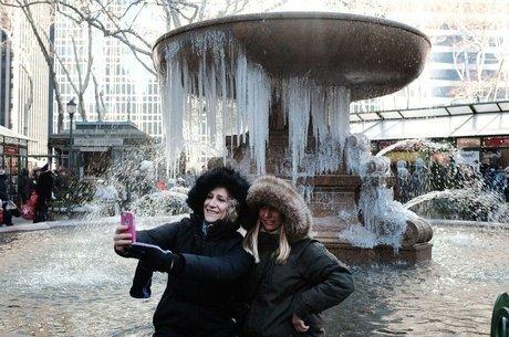 Turistas em Nova York aproveitaram para tirar fotos em frente a uma fonte congelada no Bryant Park