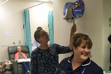 Carly Appleby tocando o sino para celebrar o fim do tratamento