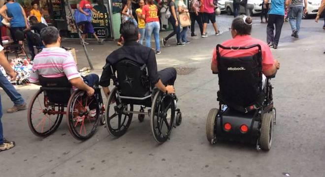Thiago Helton e outros dois cadeirantes passando pela Praça Sete