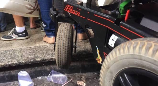 Cadeira motorizada tentando subir o degrau de um estabelecimento comercial