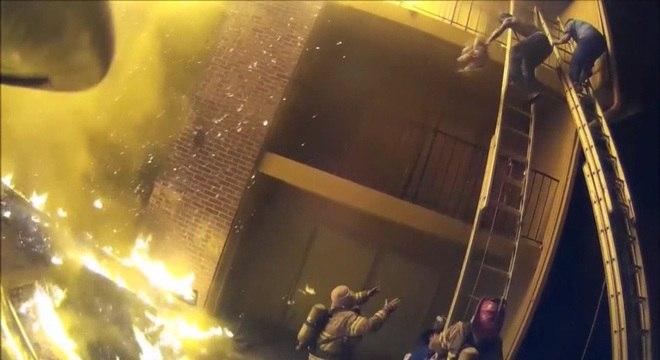 Bombeiro se prepara para segurar criança arremessada pelo pai de prédio em chamas