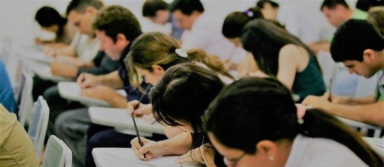Sala de aula com candidatos fazendo uma prova de concurso público