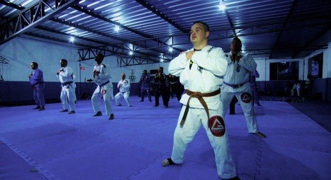 Jovem com síndrome de down no tatame entre vários praticantes de jiu-jitsu