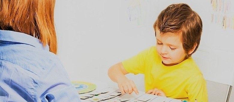 Criança manejando alguns objetos em uma mesa enquanto uma mulher observa seu comportamento.