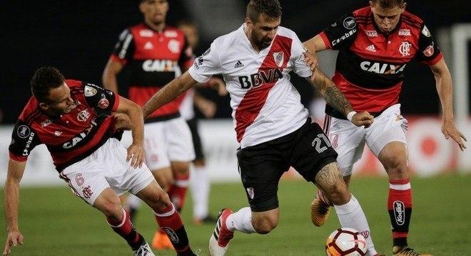 Lucas Pratto, do River Plate, tenta passar pela marcação do Flamengo