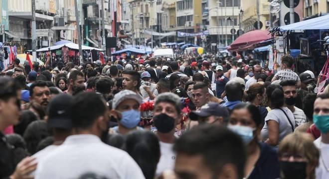 Pedestres lotam a 25 de Março, na região central de São Paulo, neste sábado (10)