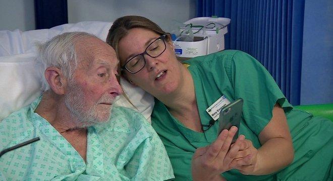 Enfermeira mostra a um paciente com lesão renal aguda os resultados de exames de sangue em seu celular