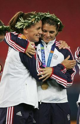 A ex-zagueira Joy Fawcett (à direita) subiu três vezes no pódio olímpico com a seleção dos Estados Unidos. Ela foi prata em Sydney 2000 e bicampeã em Atlanta 1996 e Atenas 2004.