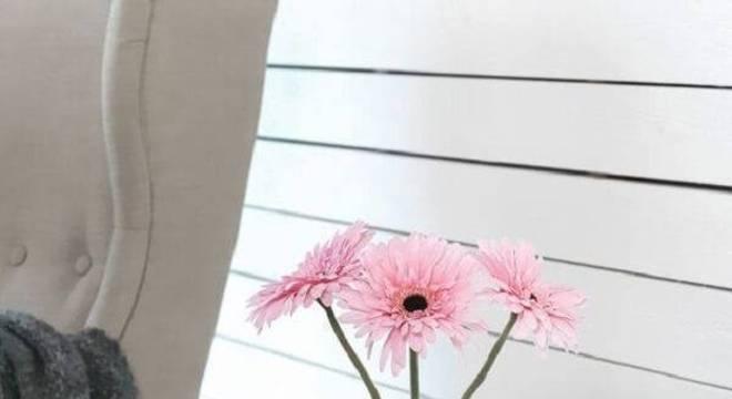 A gérbera rosa sobre o criado mudo decora o ambiente