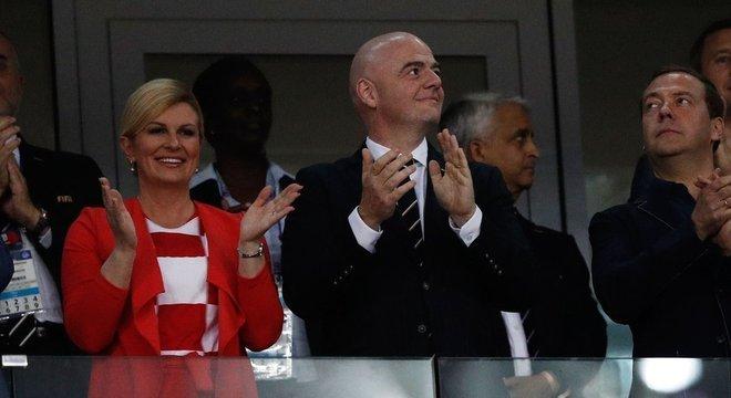 A croata assistiu à partida em que sua seleção eliminou a Rússia ao lado do presidente da Fifa, Gianni Infantino (ao centro), e do primeiro-ministro russo, Dmitry Medvedev (à direita)