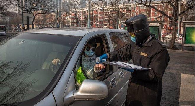 Guarda testa a temperatura corporal de um motorista em Pequim, na China