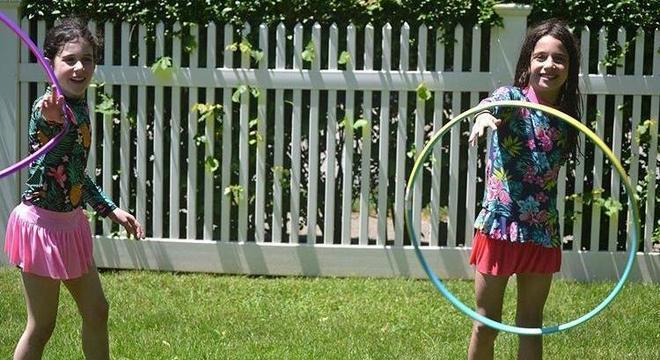 Crianças brincam no quintal como se estivessem em acampamento