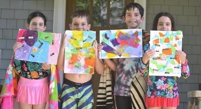 Crianças mostrando seus desenhos durante atividade em casa