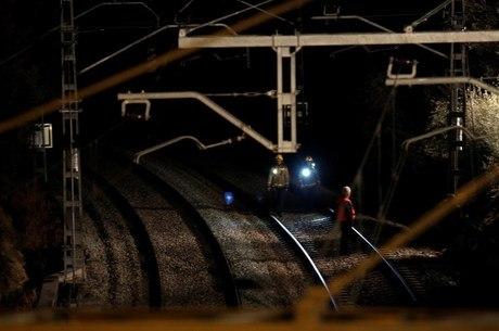 Funcionários inspecionam linha após acidente de trem