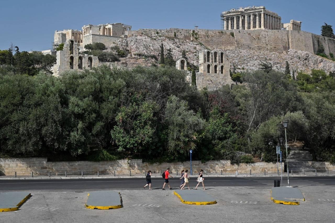 Pessoas caminham pela Acrópole deserta