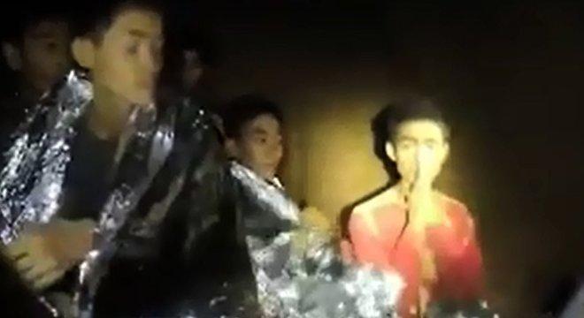 dul Samon (à direita, com as mãos unidas) chamou a atenção por cumprimentar os mergulhadores com um gesto tradicional de respeito, na tradição tailandesa. Ele se comunicou em inglês com os dois britânicos que acharam o grupo, após uma semana de buscas na caverna. Samon é refugiado de uma região de conflito de Mianmar e vive longe dos pais