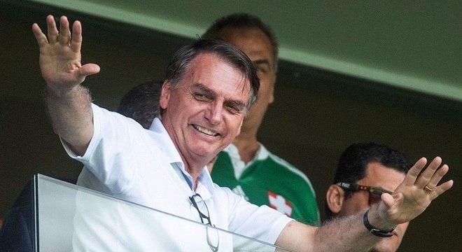 Bolsonaro acena para o público durante partida de futebol