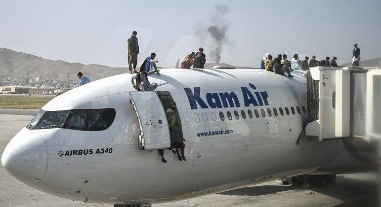 Afegãos esperam em avião para tentar fugir do aeroporto de Cabul