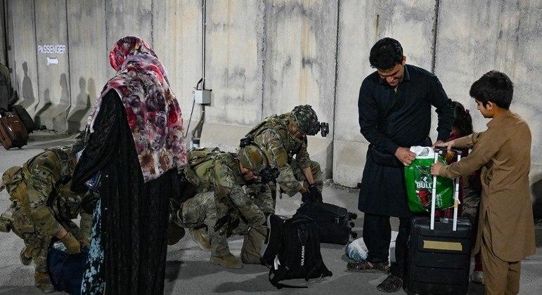 Soldados revistam pertences de refugiados afegãos no aeroporto de Cabul
