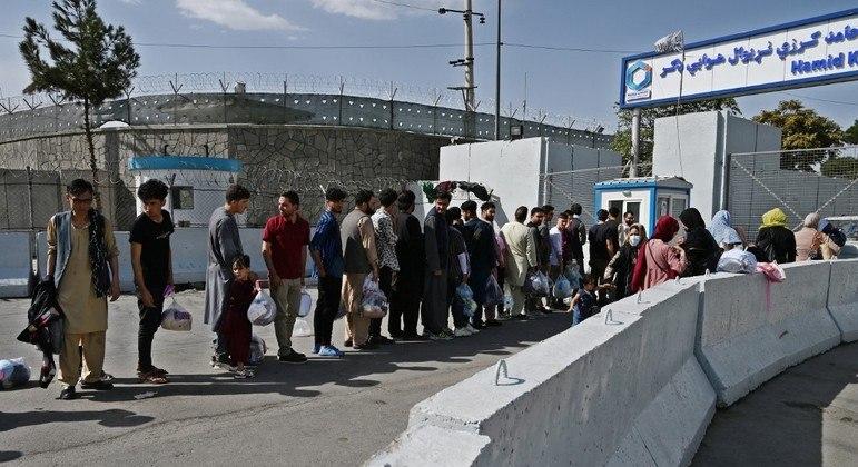 Afegãos aguardam em fila diante do aeroporto de Cabul