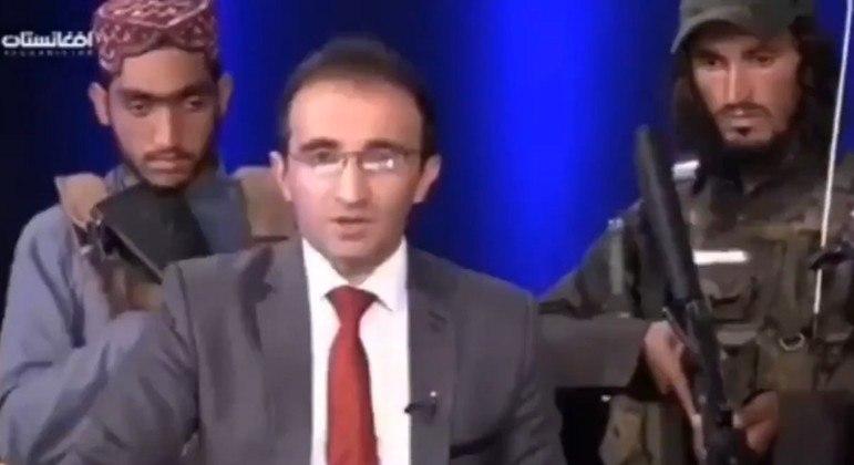 O apresentador Mirwais Heidari Haqdoost aparece cercado por talibãs no estúdio da TV Afghanistan