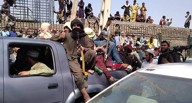 Combatentes do Taleban sentam-se em um veículo ao longo da rua na província de Jalalabad em 15 de agosto de 2021.