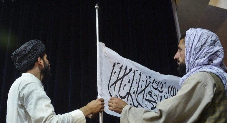 Homens do Talibã hasteiam a bandeira do grupo extremista em Cabul, capital do Afeganistão