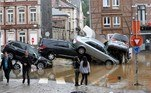 A picture taken on July 15, 2021 shows people passing by cars piled up at a roundabout in the Belgian city of Verviers, after heavy rains and floods lashed western Europe, killing at least two people in Belgium. François WALSCHAERTS / AFP