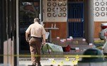 HIALEAH, FLORIDA - MAY 30: A Miami-Dade police officer walks near a body on the ground near shell case evidence markers where a mass shooting took place outside of a banquet hall on May 30, 2021 in Hialeah, Florida. Police say that two people died, and an estimated 20 to 25 people are injured after the shooting at the banquet hall rented out for a concert. Joe Raedle/Getty Images/AFP JOE RAEDLE / GETTY IMAGES NORTH AMERICA / Getty Images via AFP