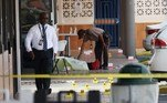 HIALEAH, FLORIDA - MAY 30: A Miami-Dade police officer replaces a body bag over a body as they investigate near shell case evidence markers on the ground where a mass shooting took place outside of a banquet hall on May 30, 2021 in Hialeah, Florida. Police say that two people died, and an estimated 20 to 25 people are injured after the shooting at the banquet hall rented out for a concert. Joe Raedle/Getty Images/AFP JOE RAEDLE / GETTY IMAGES NORTH AMERICA / Getty Images via AFP