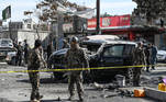 Security personnel investigate a damaged armored car at the site after multiple bomb blasts, killing at least two people, in Kabul on February 10, 2021. WAKIL KOHSAR / AFP