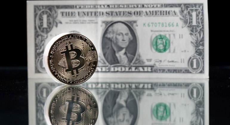 This photograph taken on April 26, 2021 in Paris shows a physical imitation of the Bitcoin crypto currency pictured with a US one dollar bank note. Martin BUREAU / AFP