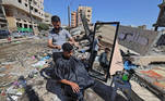 A Palestinian barber works next to the ruins of buildings and shops destroyed by Israeli strikes, in Gaza City, on May 25, 2021. A ceasefire was reached late last week after 11 days of deadly violence between Israel and the Hamas movement which runs Gaza, stopping Israel's devastating bombardment on the overcrowded Palestinian coastal enclave which, according to the Gaza health ministry, killed 248 Palestinians, including 66 children, and wounded more than 1,900 people. Meanwhile, rockets from Gaza claimed 12 lives in Israel, including one child and an Israeli soldier. MOHAMMED ABED / AFP