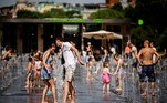 People cool off at a water fountain during a hot summer day at Gorky Park on June 21, 2021, in Moscow, where temperatures have reached 30 degrees Celsius. Dimitar DILKOFF / AFP