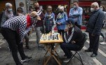 """People play chess in Pamplona during the """"Chess Run"""" tournament on July 14, 2021. Some 80 players took part in the """"Chess Run"""" in Pamplona along the same route as the traditional running of the bulls celebrated every year during the San Fermin festival that was cancelled for the second year in a row due to the Covid-19 pandemic. ANDER GILLENEA / AFP"""