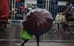 A boy shelters with an umbrella while walking along a street during a monsoon rainfall in Siliguri on June 11, 2021. Diptendu DUTTA / AFP